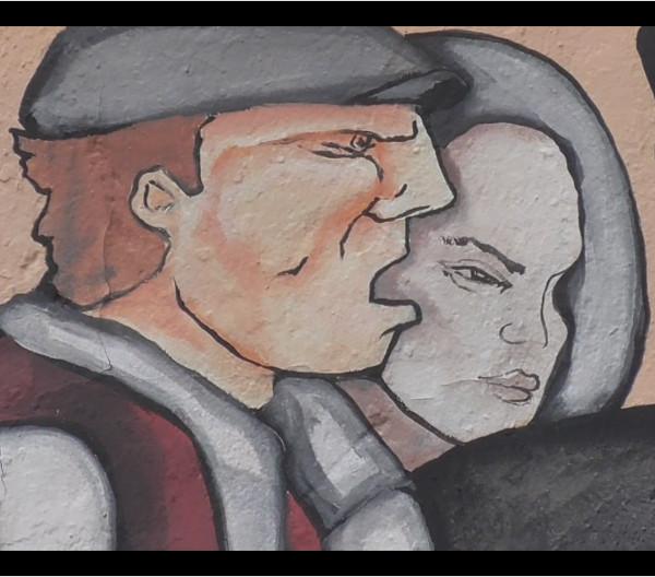 ritaglio di pittura muraria a Capo Comino raffigurante volto sardo maschile e femminile affiancato, come sagome pianeti