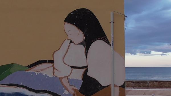 murale in Santa Lucia raffigurante donna sarda con scialle nero, mare e nuvole sulla porzione destra dell'immagine dove termina il muro