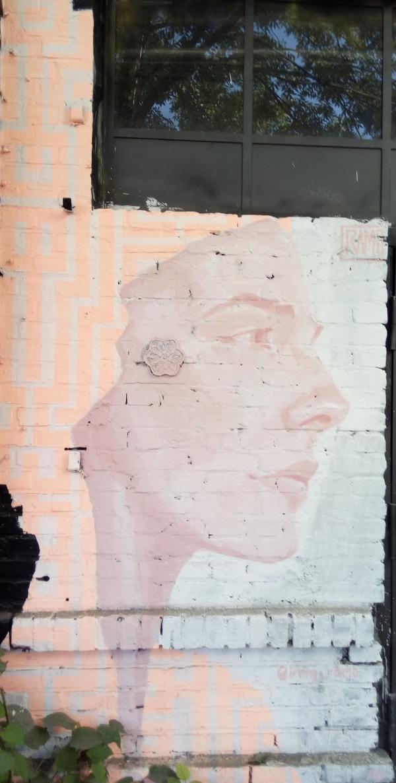 pittura muraria in Berlino raffigurante profilo destro di donna giovane su muro di mattoni decorato a tinte lievi, sopra alberi riflessi su vetri di portone metallico