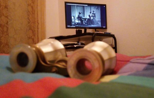 binocoli da teatro poggiati su trapunta copriletto, in secondo piano un monitor di computer che proietta la rappresentazione dell'opera in bianco e nero
