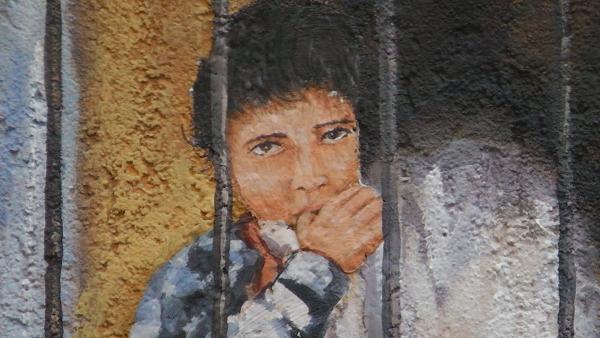 particolare di pittura muraria in Siniscola raffigurante bambina che guarda tra barre di inferriata di balcone