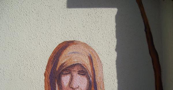 pittura muraria in Siniscola raffigurante donna anziana con velo marrone chiaro sul capo, foto tagliata in modo da nascondere la bocca, ombra di spigolo e stelo di vite a destra