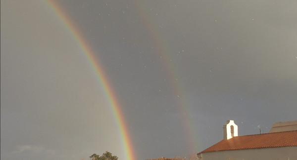 profilo della chiesetta di Santa Lucia a destra, due arcobaleni a sinistra