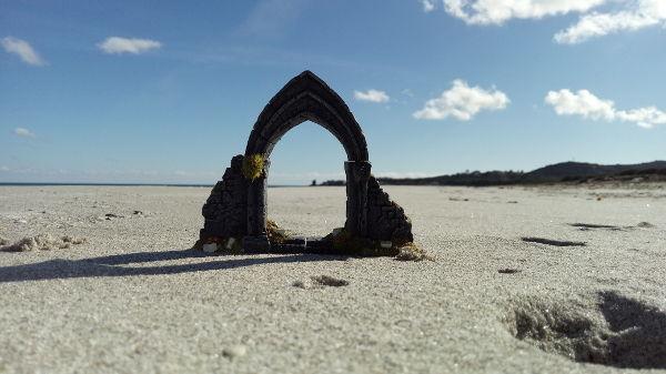 finestra gotica modellino su spiaggia incornicia la torre di Santa Lucia lontana, le pendici dei colli a destra