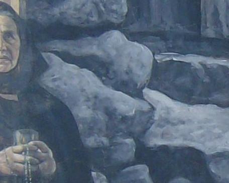 particola di pittura muraria in Fonni raffigurante la metà destra del viso di una donna in costume nero, le mani che reggono un oggetto e un rosari, un riquadro con cornice sulla destra con particolare di dipinto nel dipinto, pietre nere della facciata di una casa
