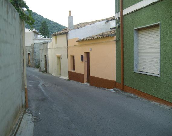 scorcio di Siniscola, strada in direzione diagonale da destra a sinistra, case a un piano variamente colorate, monte verde sullo sfondo