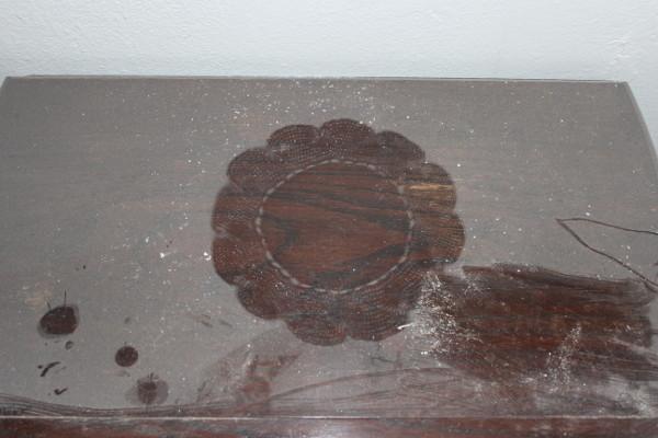 impronta di centrino su tavolino coperto da polvere fitta