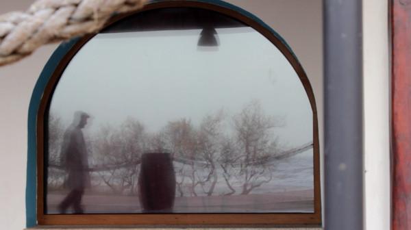 Francesco in impermeabile e berretto grigio cammina davanti vetrina a mezzaluna con alberi spogli riflessi da sinistra, tutto sfocato